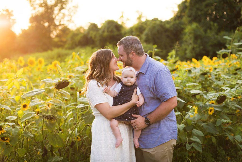 houston family posing in front of sunflower field