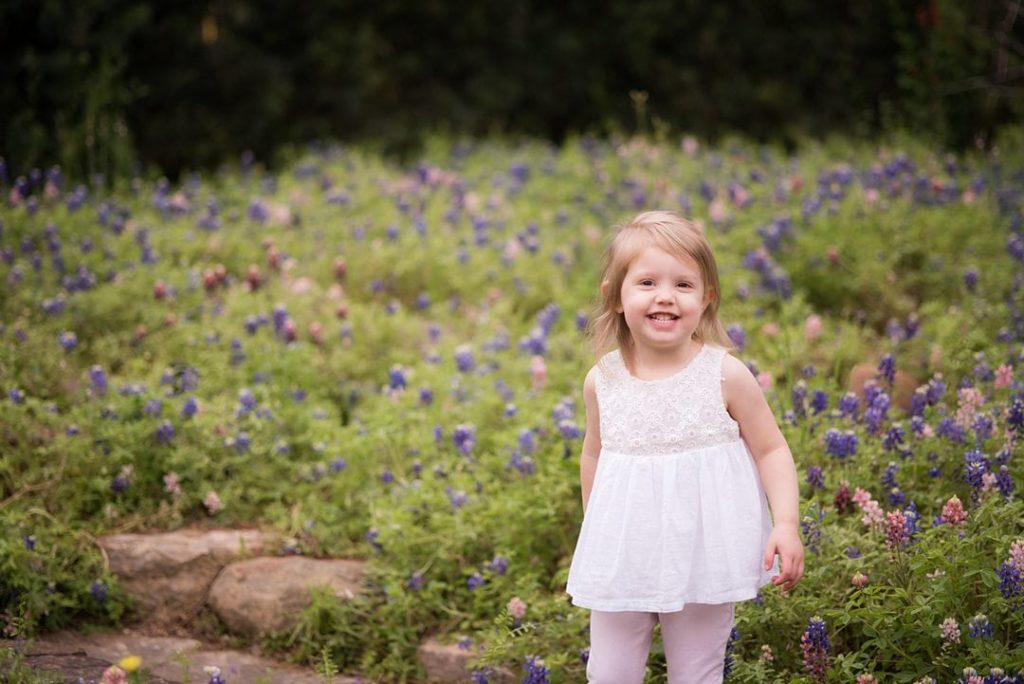 houston child smiling for photo in front of bluebonnets